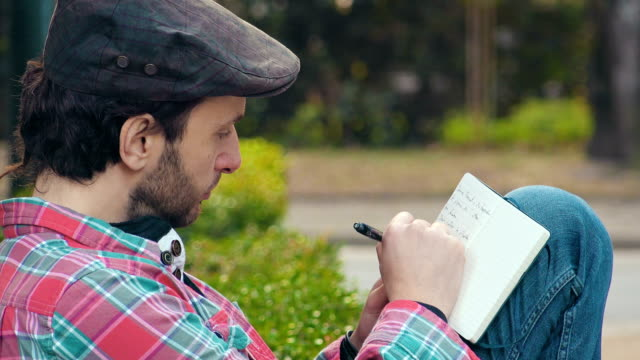 young writer writes on the diary at the park video
