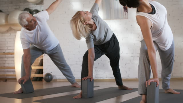 Young Yoga Teacher Doing Asanas with Client Couple Tilting up medium shot of young Caucasian woman teaching yoga class for mature client couple, doing triangle pose together with them while talking and giving instructions for next asana prop stock videos & royalty-free footage