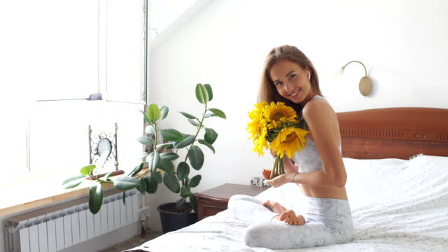 Young yogi woman with sunflower on bed in home