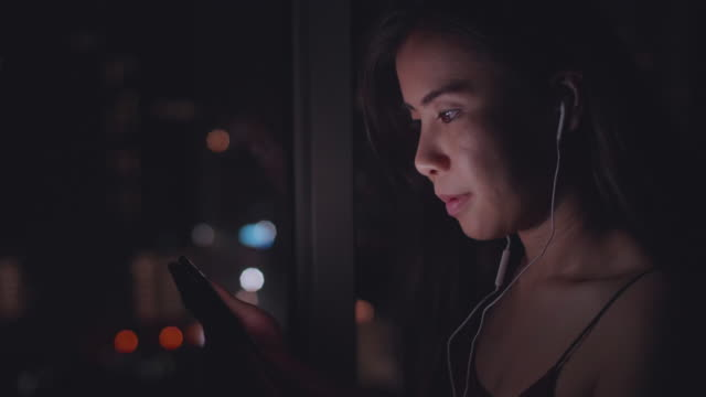 Youngasian woman  Listening To Music On Phone At Night