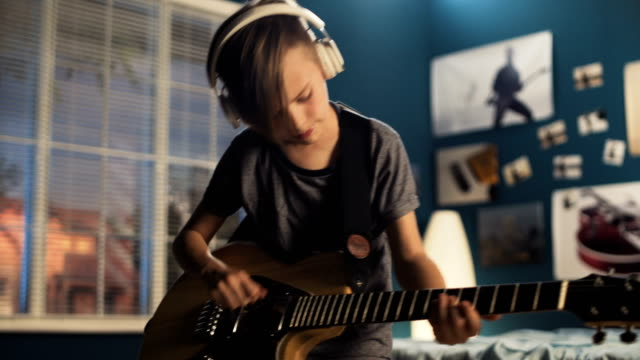 Youngster with guitar in bedroom