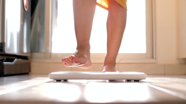 ung kvinna steg till vikt skala - black woman towel workout bildbanksvideor och videomaterial från bakom kulisserna