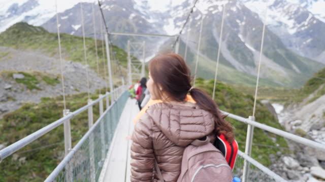 vídeos y material grabado en eventos de stock de youngwoman camina en puente colgante - nueva zelanda