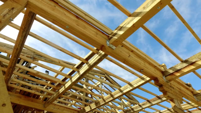 your dream home. new residential construction house framing against a blue sky - intelaiatura video stock e b–roll