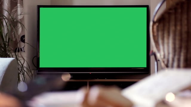 TV Your message, chroma keyed     ID Dolly video clip taken in a living room showing a large TV screen, a hand holding a remote control turns it on to reveal a green screen for your message, video or advert. The TV screen then REMAINS STATIONARY & DOESN'T CHANGE SHAPE from a perfect rectangle. Chroma keyed panel to advertise in this home environment. living room stock videos & royalty-free footage