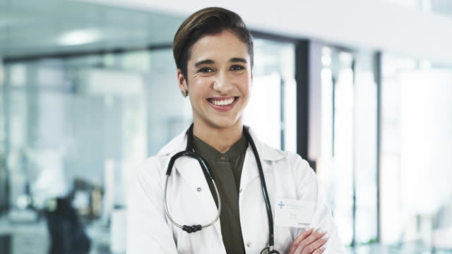 Your wellbeing is exactly why I'm here 4k video footage of an attractive young female doctor smiling while standing with her arms crossed in a hospital female doctor stock videos & royalty-free footage