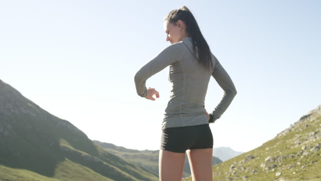 You're not where you used to be, embrace that! 4k video footage of a young woman checking the time from a mountain top after her run arms akimbo stock videos & royalty-free footage