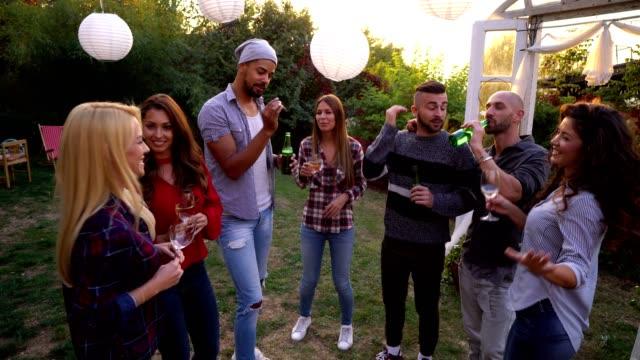 vídeos de stock, filmes e b-roll de juventude em uma reunião social no quintal - festa no jardim
