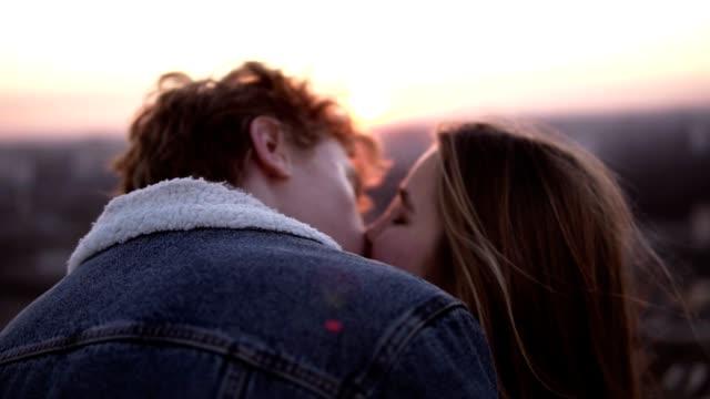 年輕夫婦享受一個浪漫的吻, 而站在風大的高屋頂與城市的背景。城市景觀 - 浪漫 個影片檔及 b 捲影像