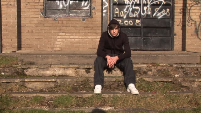 Youth / Hoody sat on steps, Bored, With Graffiti video