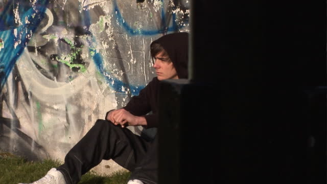 Youth / Hoody sitting around with Grafitti behind - DOLLY video
