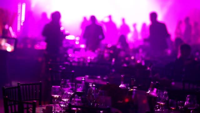 vidéos et rushes de un groupe de jeunes dans un restaurant ou une boîte de nuit, tables de banquet avec l'alcool et la nourriture dans le contexte des silhouettes de danser les gens, stade léger et remplissage violet - banquet