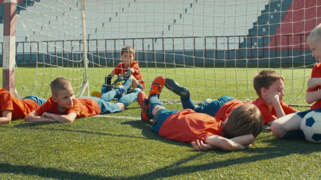 Youth soccer team before training Little boys in professional soccer uniform laying on the grass near goal post at stadium and waiting for the start of training goal post stock videos & royalty-free footage