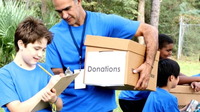 youth sport team samlar in objekt för katastrofhjälp - välgörenhet bildbanksvideor och videomaterial från bakom kulisserna