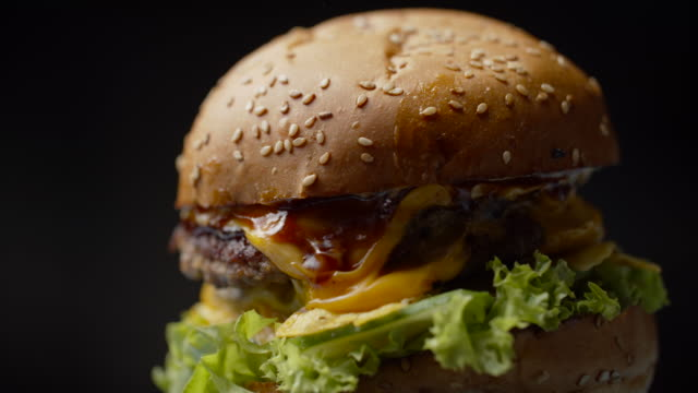Yummy burger with double beef cutlet, melted cheese, lettuce and vegetables rotating on dark background in slow motion.