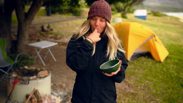 Yummy! 4k video footage of an attractive young woman standing and eating avocado out of a bowl during a camping trip avocado stock videos & royalty-free footage