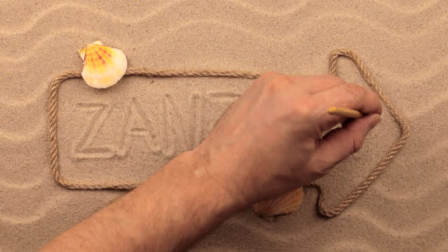 Zanzibar inscription written by hand on the sand, in the pointer made from rope. video