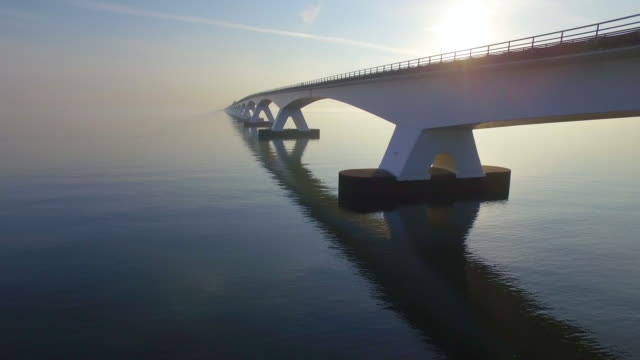 Zeeland Bridge The Zeelandbrug during sunrise. The sun is already a bit higher in the sky and it's reflected in the water of the North sea. The bridge is also reflected in the water. Cars drive at a high speed over it. dutch architecture stock videos & royalty-free footage