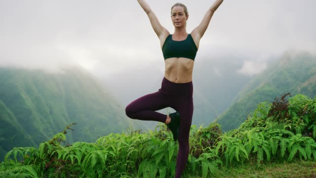 Zen yoga goddess finding her inner calm Beautiful fitness woman performs yoga pose on lush mountain top mindfulness stock videos & royalty-free footage