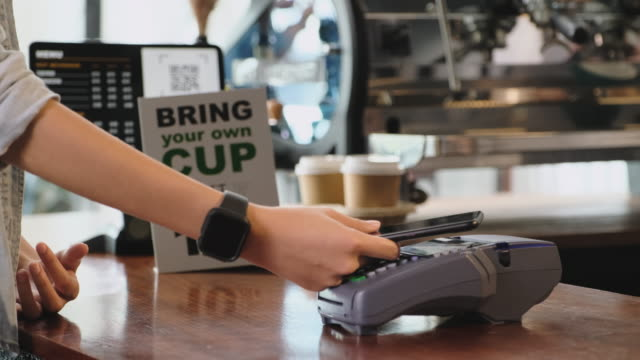 zero waste lifestyle concept.slow moiton close up hand of asian woman customer bring own cup to buy coffee and pay contactless with mobile phone to barista on counter bar at cafe - sustainability video stock e b–roll