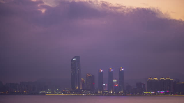 zhuhai city coastline sunset night illuminated hotel resort complex panorama timelapse 4k china - zhuhai video stock e b–roll