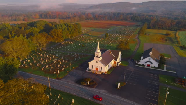 Zion United Lutheran Church and cemetery at sunrise. Brodheadsville, Poconos region, Pennsylvania. Aerial drone video with the static camera.