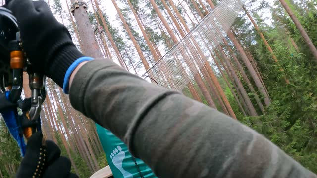 zip line aerial runway. Rope park in pine forest. First person view. extreme