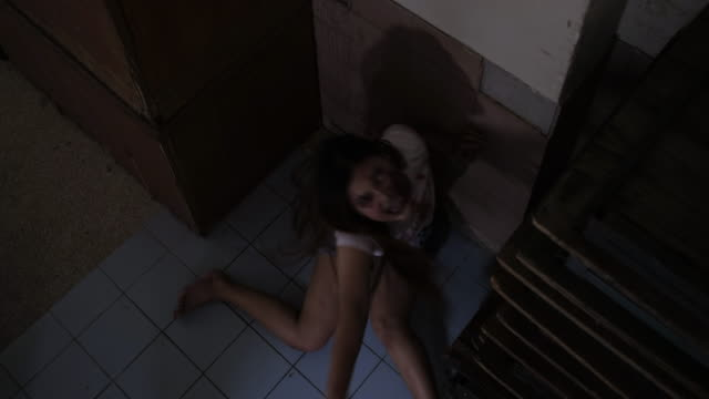 Zombie characters ghost woman revive on floor in dark house horror halloween at nightmare, Female evil screaming monster in night background infected with bleed movie scene film in holiday festival.