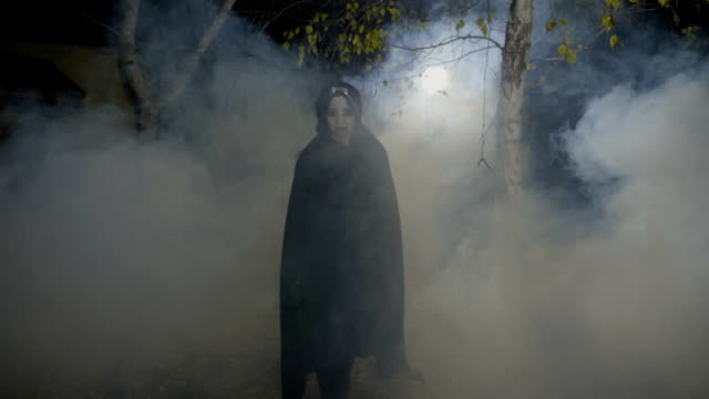 Zombie female vampire smiling maleficent and walking among trees on halloween moonlight video
