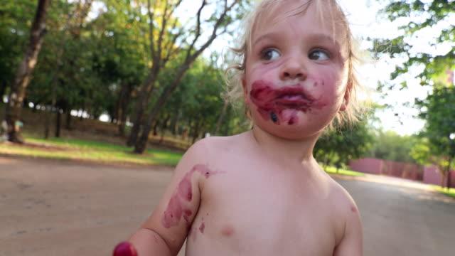 vídeos de stock e filmes b-roll de zombie like infant toddler. baby boy looking like a living dead character after having eaten dozens of berries outdoors - boca suja