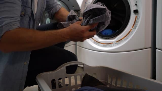 Zoom en cas client méconnaissable à une laverie automatique, chargement de la machine à laver - Vidéo