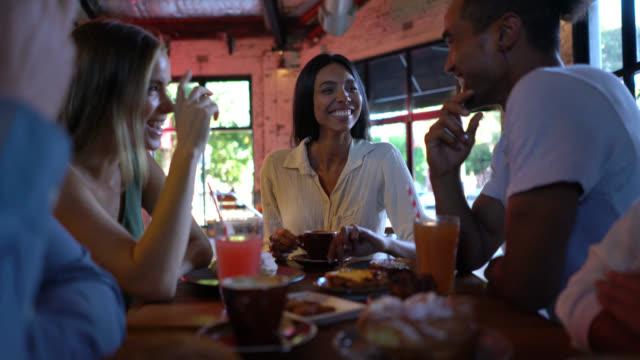 vídeos y material grabado en eventos de stock de zoom de una hermosa mujer disfrutando de café y aperitivos con sus amigos en una panadería mirando feliz - comida francesa