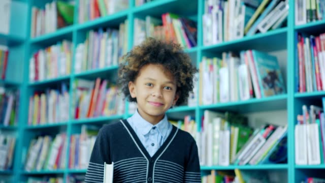 Zoom in of handsome mixed race little boy with curly hair smiling at camera standing near shelves in school library and holding book under his arm