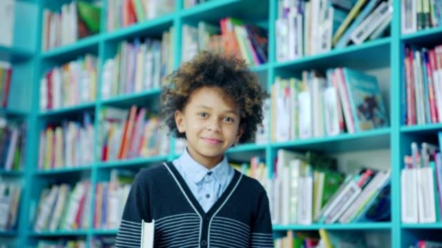 stockvideo's en b-roll-footage met zoom in van knappe mixed race kleine jongen met krullend haar glimlachen bij camera staande in de buurt van planken in de schoolbibliotheek en holding boek onder zijn arm - schooljongen