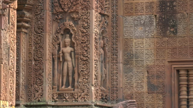 zoom in on a bas relief carving of a devata at banteay srei in angkor
