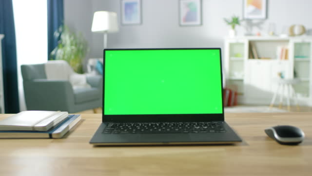 vídeos de stock e filmes b-roll de zoom in on a modern laptop with green mock-up screen display standing on the desk of the cozy living room. - computador portátil