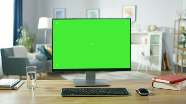 vídeos y material grabado en eventos de stock de hacer zoom en un moderno ordenador personal con pantalla verde de maqueta permanente en el escritorio de la oficina de hogar acogedor. living comedor creado por el diseñador de interiores con estilo y buen gusto. - efecto zoom