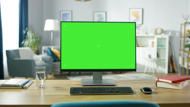 zoom in on a modern personal computer with mock-up green screen display standing on the desk of the cozy home office. living room created by interior designer with good taste and style. - zielony kolor filmów i materiałów b-roll
