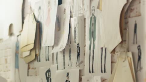 stockvideo's en b-roll-footage met zoom in op een muur met gespelde mode tekeningen en schetsen, sjablonen opknoping op de muur. - ontwerp