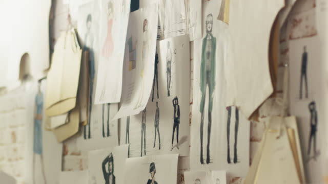 Zoom In On a Wall with Pinned Fashion Drawings and Sketches, Templates Hanging on the Wall. video
