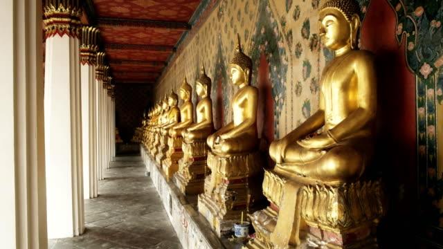 vídeos y material grabado en eventos de stock de captura de estatuas de buda en un claustro en el templo de wat arun, bangkok - sudeste