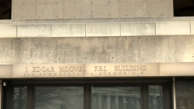 zoom in on engraving above the entrance to the fbi building in washington - quartiere generale video stock e b–roll