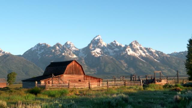 納屋とグランド ・ ティトンのショットでの日の出、ワイオミング ズームインします。 - 牧畜場点の映像素材/bロール