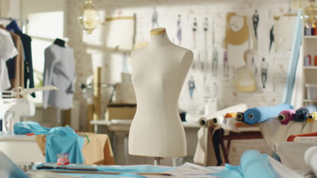 Zoom In Shot of a Tailoring Mannequin that Stands in a Bright and Sunny Studio. Various Sewing Items and Colourful Fabrics Laying around, Mannequins Standing, and Sketches Pinned to the Wall. video