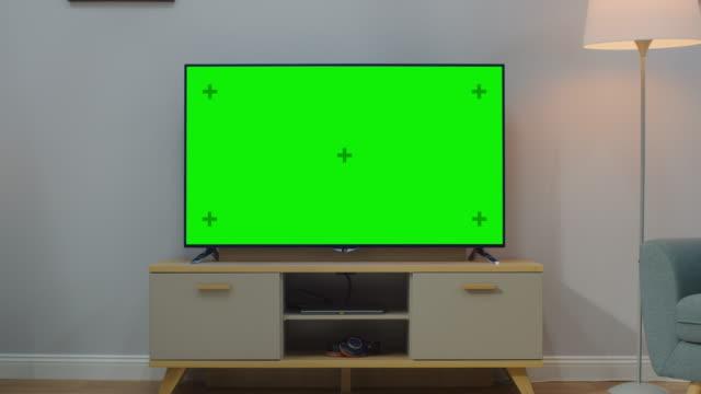 vídeos y material grabado en eventos de stock de zoom in shot de un televisor con pantalla verde horizontal maqueta. acogedora sala de estar en la hora del día con una silla y lámparas se enciende en casa. - monitor