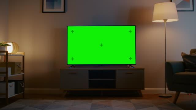 vídeos de stock, filmes e b-roll de zoom em tiro de uma tv com tela verde horizontal mock up. sala de visitas cozy da noite com uma cadeira e as lâmpadas giradas sobre em casa. - television