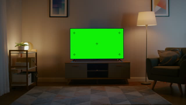 Zoom In Shot of a TV with Horizontal Green Screen Mock Up. Cozy Evening Living Room with a Chair and Lamps Turned On at Home.
