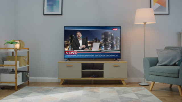 Zoom In Shot of a TV with Live News Channel. Cozy Living Room at Day Time with a Chair and Lamps Turned On at Home.