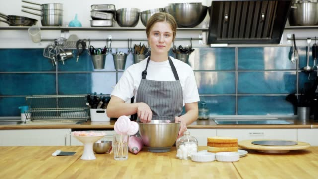 vídeos de stock e filmes b-roll de zoom in shot of beautiful female pastry chef mixing whipped cream icing for cake in bowl and smiling at camera standing at table in restaurant kitchen - avental