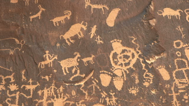 zoom in shot on a drawing of a human figure hunting sheep at newspaper rock